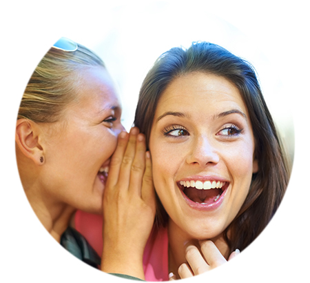 A young woman whispering a secret in her friend's ear